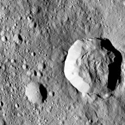 Ceres' surface shows evidence for different types of flows that indicate the presence of ice in the regolith. One type of flow encircles the large impact crater at right in this image taken by NASA's Dawn spacecraft.