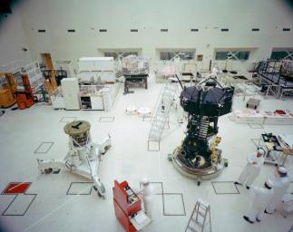 This archival photo shows the Voyager Proof Test Model (in the foreground right of center) undergoing a mechanical preparation and weight center of gravity test at NASA's Jet Propulsion Laboratory, Pasadena, California, on January 12, 1977.