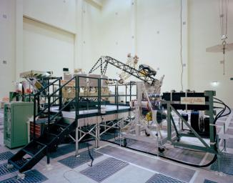 This archival photo shows the system test configuration for NASA's Voyager on October 1, 1976. The spacecraft's 10-sided bus is visible behind the catwalk railing in the foreground.