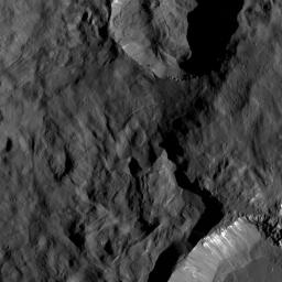 This image taken by NASA's Dawn spacecraft presents two small craters on Ceres, located in the vicinity of Toharu Crater. Juling appears at the top and Kupalo at bottom. Both craters are relatively young, as indicated by their sharp rims.