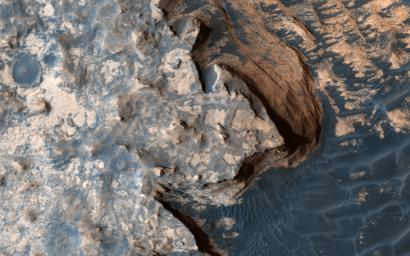 This image from NASA's Mars Reconnaissance Orbiter is of a rugged and open terrain of a stark shore-line in Meridiani Planum, giving the impression of a cloud-covered cliff edge with foamy waves crashing against it.