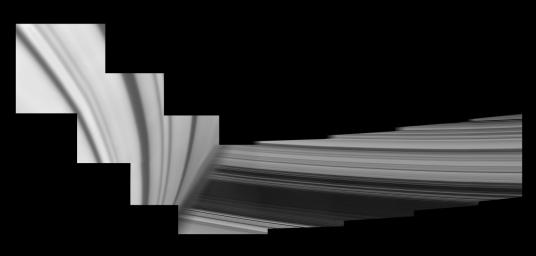 Saturn looms in the foreground of this mosaic of NASA's Cassini images, taken by the spacecraft on May 28, 2017. The planet is adorned by ring shadows. The icy rings emerge from behind the planet. Cassini ended its mission on Sept. 15, 2017.