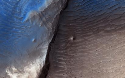 Geologists aren't quite sure what to make of the dark splotch in the middle of this image from NASA's Mars Reconnaisance Orbiter (MRO), one of several similar dark splotches that extend east and west for over 100 kilometers.