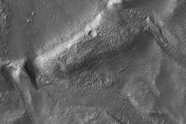 This image from NASA's Mars Reconnaissance Orbiter shows a roundish crater with three channels breaching the rim and extending to the south. The crater has been filled by sediments and may have been an ancient lake.