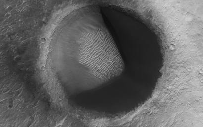 This image from NASA's Mars Reconnaissance Orbiter shows barchan sand dunes, common on Mars often forming vast dune fields within very large (tens to hundreds of km) impact basins. The regions upwind of barchans are usually devoid of sandy bedforms.