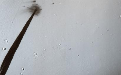 This image from NASA's Mars Reconnaissance Orbiter captured an impact crater that triggered a slope streak. When the meteoroid hit the surface and exploded to make the crater, it also destabilized the slope and initiated this avalanche.