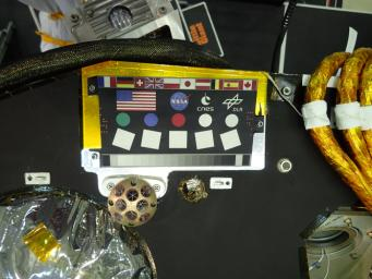 A camera calibration target sits on the deck of the NASA's InSight lander, adorned with the flags of different nations participating in the mission.