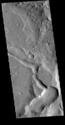 This image from NASA's Mars Odyssey is located in Terra Sabaea near the margin of Syrtis Major Planum. The channel-like feature at bottom is an unnamed. There is a high spot within the channel that would not let a fluid pass from one side to the other.
