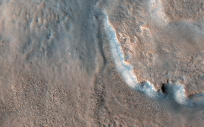 NASA's Mars Reconnaissance Orbiter shows an impact crater, home to fan-shaped deposits that extend from the rim and sit on the interior crater floor. Thick beds with varying tone are exposed along the edge of the fan.