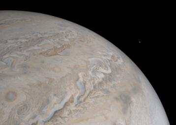 Jupiter's moon Io rises just off the horizon of the gas giant planet in this image from NASA's Juno spacecraft.