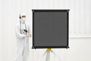 Engineer Chris Chatellier stands next to a target board with 1,600 dots, used to calibrate the forward-facing cameras on the Mars 2020 rover.