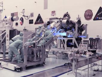 Technicians at NASA's Kennedy Space Center in Florida perform a fit check between the Mars 2020 Perseverance rover and its Multi-Mission Radioisotope Thermoelectric Generator on April 16-17, 2020.