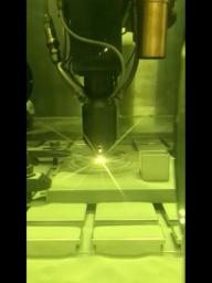 This video clip shows a 3D printing technique where a printer head scans over each layer of a part, blowing metal powder which is melted by a laser.