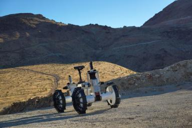 The DuAxel rover is seen here participating in field tests in the Mojave Desert. The four-wheeled rover is composed of two Axel robots. One part anchors itself in place while the other uses a tether to explore otherwise inaccessible terrain.