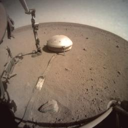 NASA's InSight lander used a scoop on its robotic arm to begin trickling soil over the cable connecting its seismometer to the spacecraft on March 14, 2021. Scientists hope insulating it from the wind will make it easier to detect marsquakes.