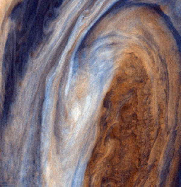 This view of the Great Red Spot is seen in greatly exaggerated color. The colors do not represent the true hues seen in the Jovian atmosphere but have been produced by special computer processing to enhance subtle variations in both color and shading.