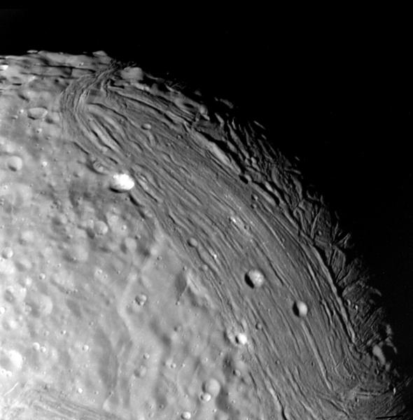 Miranda reveals a complex geologic history in this view, acquired by NASA's Voyager 2 on Jan. 24, 1986, around its close approach to the Uranian moon. At least three terrain types of different age and geologic style are evident.