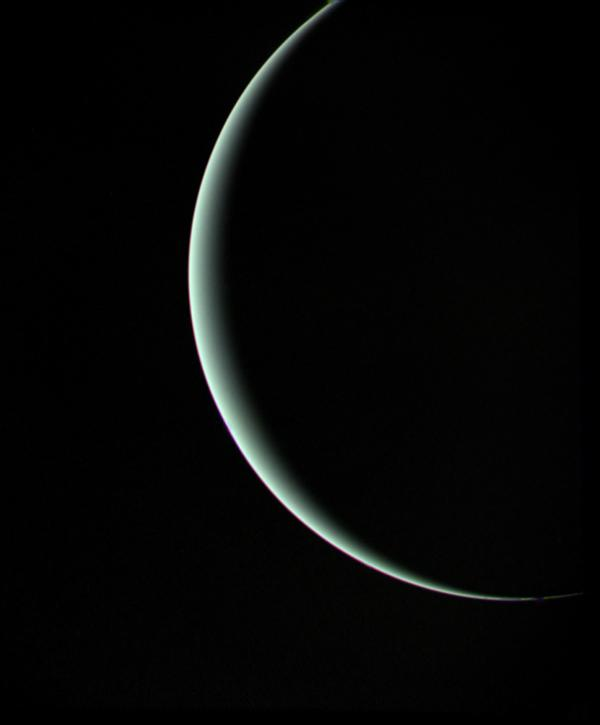 This view of pale blue-green Uranus was recorded by NASA's Voyager 2 on Jan 25, 1986, as the spacecraft left the planet behind. The thin crescent of Uranus is seen here between the spacecraft, the planet and the Sun.