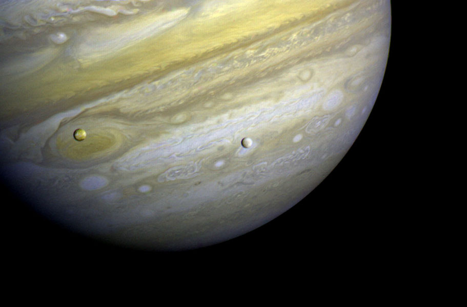 NASA's Voyager 1 took this photo of Jupiter and two of its satellites (Io, left, and Europa) on Feb. 13, 1979. Io is above Jupiter's Great Red Spot; Europa is above Jupiter's clouds. The poles are dark and reddish.