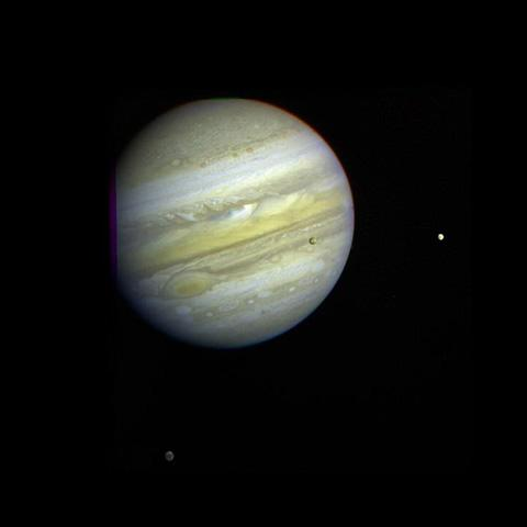 Jupiter, its Great Red Spot and three of its four largest satellites are visible in this photo taken Feb. 5, 1979, by Voyager 1. Io, Europa, and Callisto are seen against Jupiter's disk.