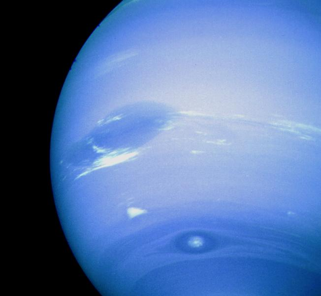 This photograph of Neptune was reconstructed from two images taken by NASA's Voyager 2. At the north (top) is the Great Dark Spot, accompanied by bright, white clouds that undergo rapid changes in appearance.