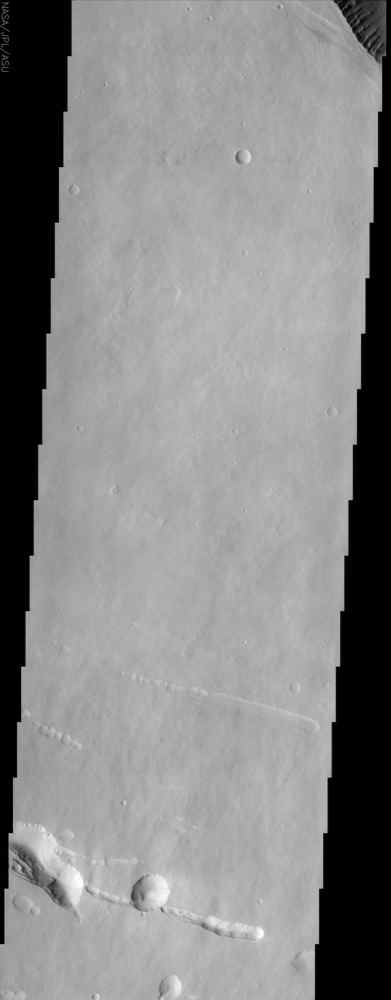 At the top right of this NASA Mars Odyssey image, the rim of the caldera of Pavonis Mons, one of four exceptionally large volcanoes in the Tharsis region, is barely visible with steep cliffs formed by the collapse of a portion of the volcano's summit.