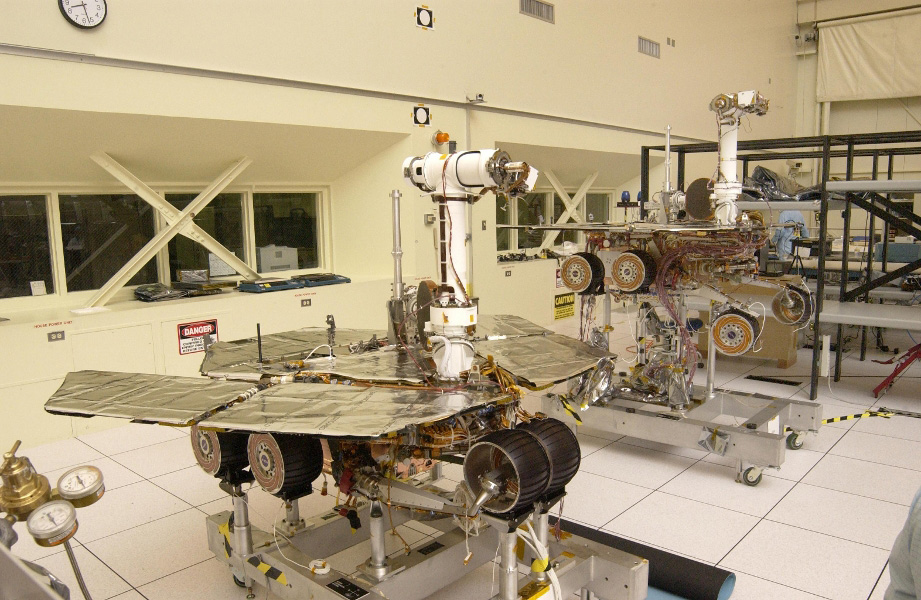 The twin rovers sit side-by-side in different stages of deployment. NASA's Rover 2's (left) front wheels are stowed, while NASA's Rover 1's front wheels are deployed.