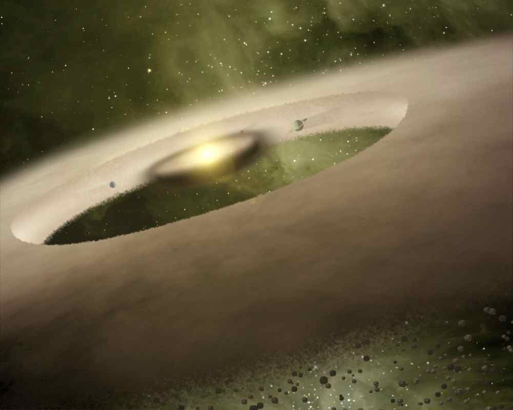 This artist's concept is of the one-million-year-old star system called UX Tau A, approximately 450 light-years away. NASA's Spitzer Space Telescope showed a gap in the dusty planet-forming disk swirling around the system's central sun-like star.