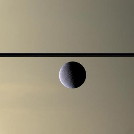 The Cassini spacecraft looks toward Rhea's cratered, icy landscape with the dark line of Saturn's ringplane and the planet's murky atmosphere as a background. Rhea is Saturn's second-largest moon, at 1,528 kilometers (949 miles) across.