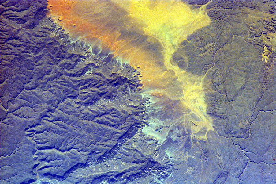 The impermanent waterways shown here from NASA's EarthKAM are part of Oued Irharrhar, which appear to be carrying sulfur (yellow) and iron (red) deposits. The city of Amguid is located on these waterways, and all lie in the Mouydir Mountains in Algeria.