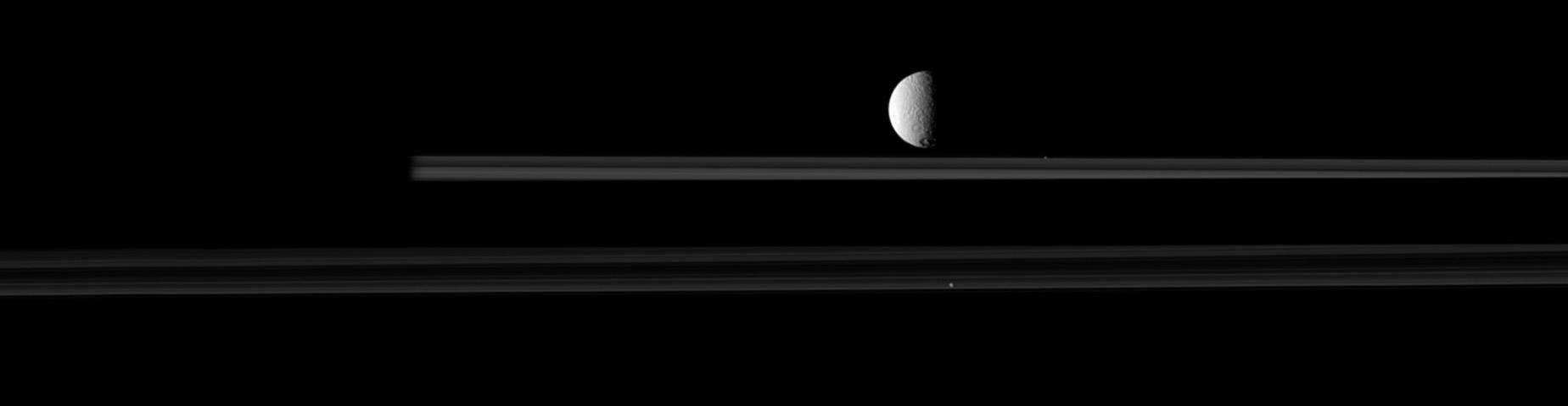 The moon Tethys is upstaged by two smaller moons, Pandora and Prometheus, in this image from NASA's Cassini spacecraft. Go to the Photojournal to view the animation.