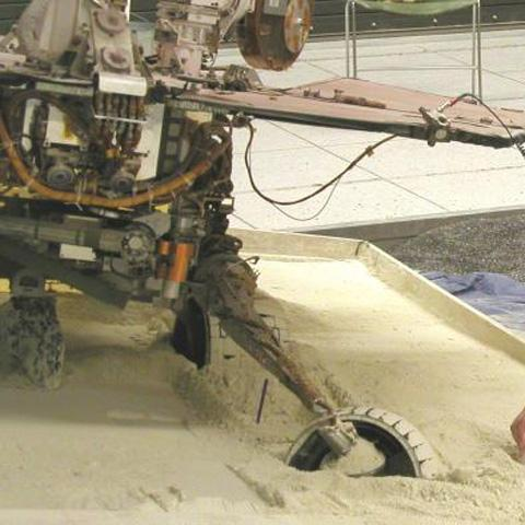 Mars Exploration Rover team members at NASA's Jet Propulsion Laboratory, Pasadena, Calif., prepare an experiment on July 13, 2009, for assessing how a test rover moves when embedded in loose soil and commanded to drive backward with wheels turned.