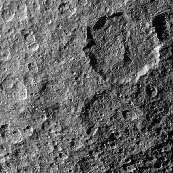 The two large craters on the right of this image are overprinted with smaller, more recent craters of Saturn's moon Rhea in this view from NASA's Cassini spacecraft.