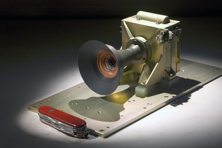 A pocketknife provides scale for this image of the Mars Descent Imager camera; the camera will fly on the Curiosity rover of NASA's Mars Science Laboratory mission. Malin Space Science Systems, San Diego, Calif., supplied the camera for the mission.