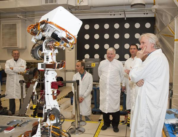 A group of members from the Jet Propulsion Laboratory watch the motions of an engineering model of the camera mast for NASA's Mars rover Curiosity on March 5, 2010.