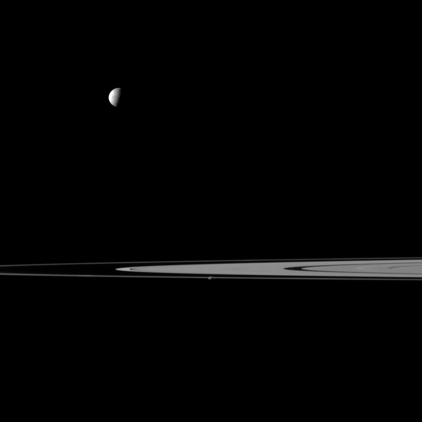 Saturn's rings lie between a pair of moons in this view from NASA's Cassini spacecraft that features Mimas and Prometheus. Mimas is the more noticeable of the two moons at top left, Prometheus is near the center of image and closest to Cassini.