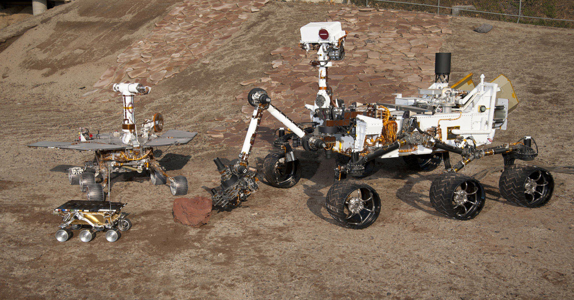 This grouping of two test rovers and a flight spare provides a graphic comparison of three generations of Mars rovers developed at NASA's Jet Propulsion Laboratory, Pasadena, Calif. The setting is JPL's Mars Yard testing area.
