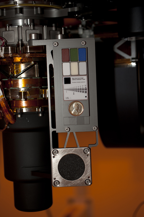 Two instruments at the end of the robotic arm on NASA's Mars rover Curiosity will use calibration targets attached to a shoulder joint of the arm. The penny is a size reference giving the public a familiar object for perceiving size on Mars easily.