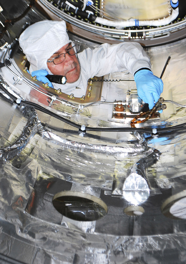 A spacecraft technician is performing closeout work inside the fairing that will be installed around NASA's Nuclear Spectroscopic Telescope Array (NuSTAR) spacecraft in a processing facility at Vandenberg Air Force Base in California.