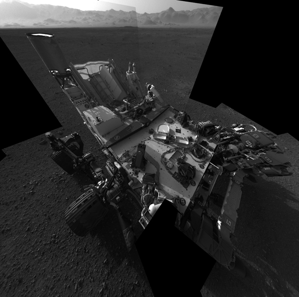 This full-resolution self-portrait shows the deck of NASA's Curiosity rover. The back of the rover can be at top left, two of the right side wheels at left, and the undulating rim of Gale Crater forms the lighter color strip in the background.