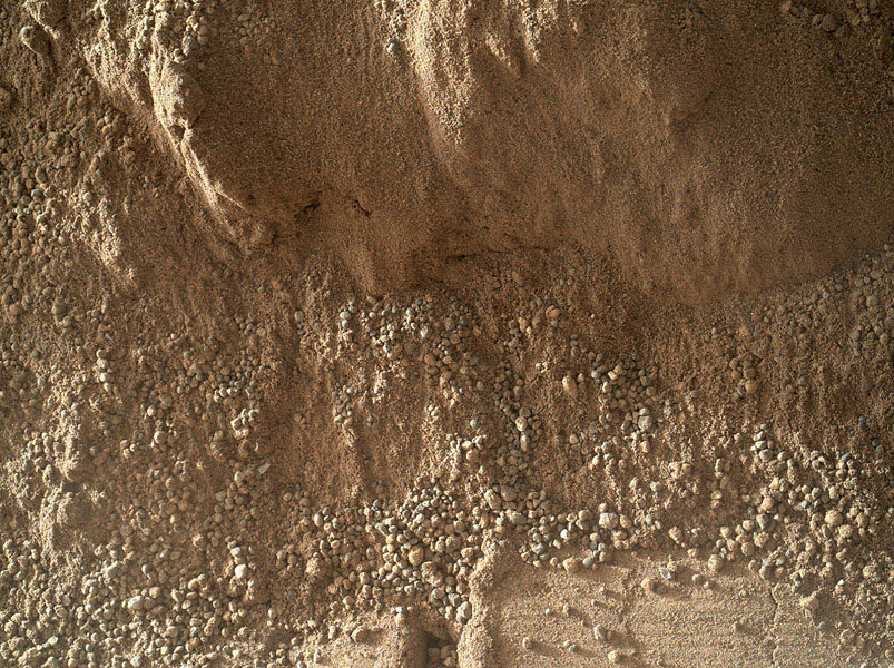 This image shows the wall of a scuffmark NASA's Curiosity made in a windblown ripple of Martian sand with its wheel. The upper half of the image shows a small portion of the side wall of the scuff and a little bit of the floor of the scuff.