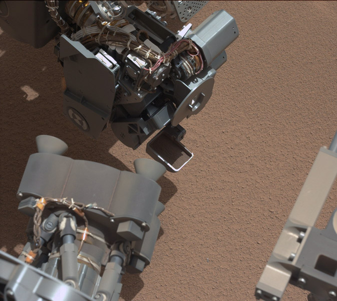 This image from NASA's Curiosity shows a scoop full of sand and dust lifted by the rover's first use of the scoop on its robotic arm. In the foreground, near bottom of this image, the bright object visible on the ground might be a piece of rover hardware.