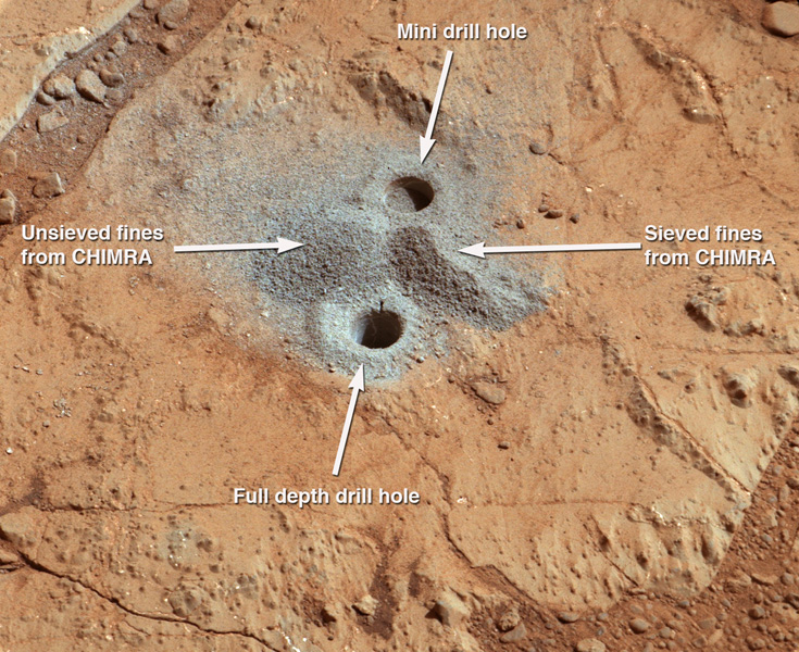 This image shows the first holes into rock drilled by NASA's Mars rover Curiosity, with drill tailings around the holes plus piles of powdered rock collected from the deeper hole and later discarded.