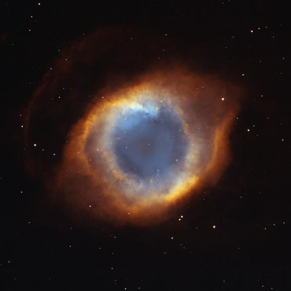 This image of the Helix Nebula from NASA's Hubble Space Telescope shows a fine web of filamentary 'bicycle-spoke' features embedded in the colorful red and blue gas ring, which is one of the nearest planetary nebulae to Earth.