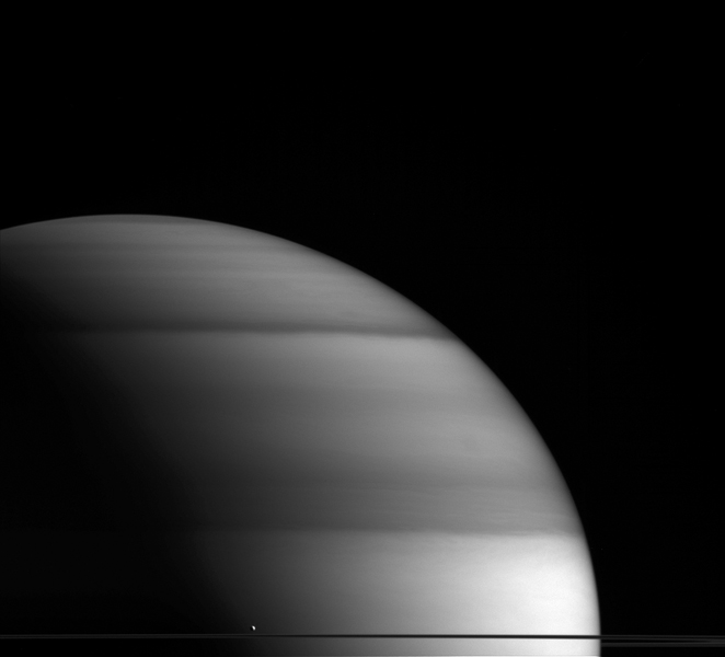 The water-world Enceladus appears here to sit atop Saturn's rings like a drop of dew upon a leaf in this view from NASA's Cassini spacecraft.