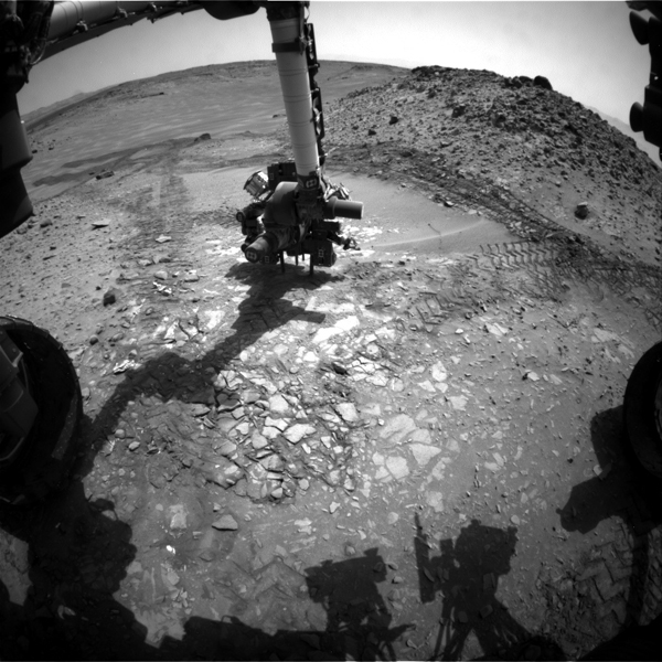 This image from the front Hazcam on NASA's Curiosity Mars rover shows the rover's drill in place during a test of whether the rock beneath it, 'Bonanza King,' would be an acceptable target for drilling to collect a sample.