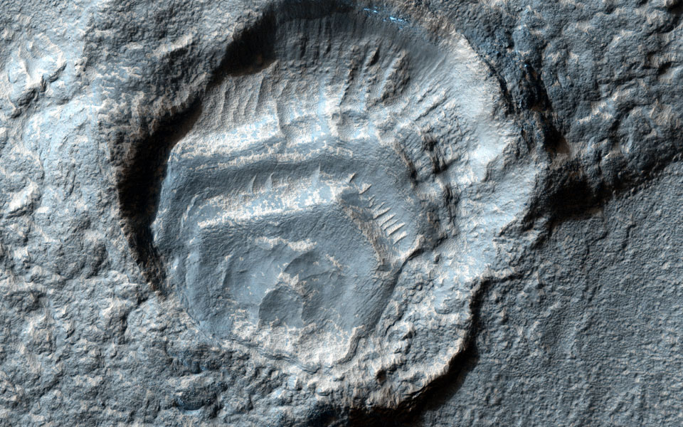 This crater captured by NASA's Mars Reconnaissance Orbiter has a strange appearance, as if the crater has feet with toes sticking out of two sides, likely caused by a highly oblique impact event.