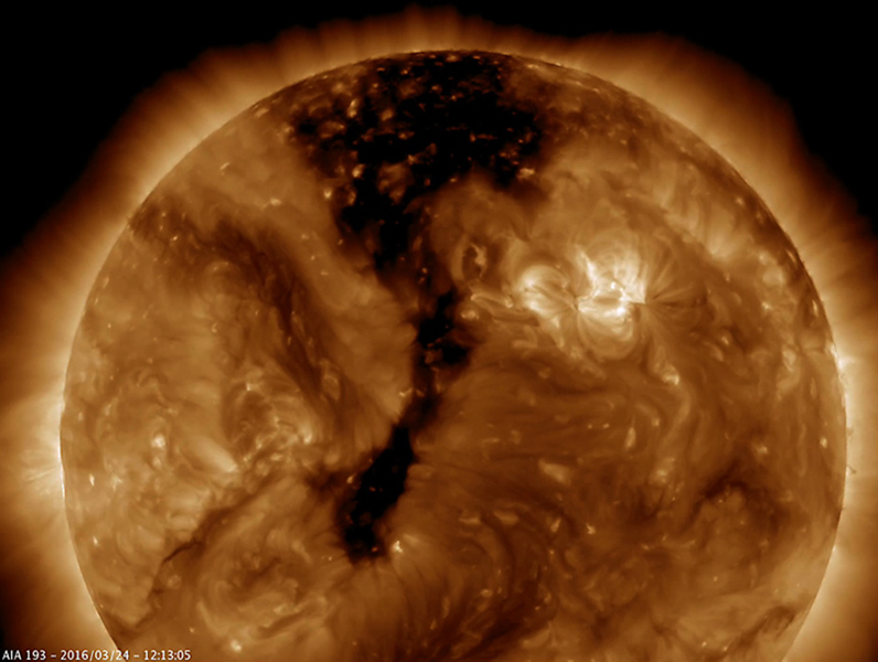 NASA's Solar Dynamics Observatory shows a long coronal hole has rotated so that was temporarily facing right towards Earth (Mar. 23-25, 2016). Coronal holes appear dark when viewed in some wavelengths of extreme ultraviolet light.