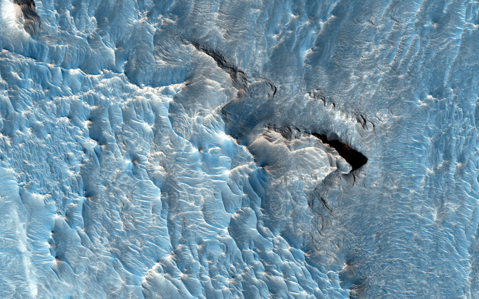 The objective of this observation from NASA's Mars Reconnaissance Orbiter is to examine a light-toned deposit in a region of what is called 'chaotic terrain.' Some shapes suggest erosion by a fluid moving north and south.