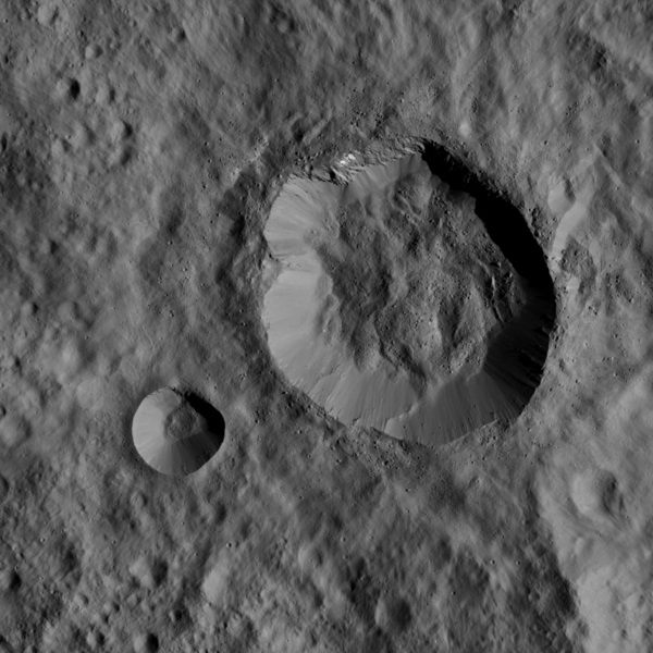 This image, taken by NASA's Dawn spacecraft on Jan. 1, 2016, shows two relatively young, fresh craters on Ceres. Large blocks of ejected material fell near the rims of the craters and onto the floor of the larger crater.
